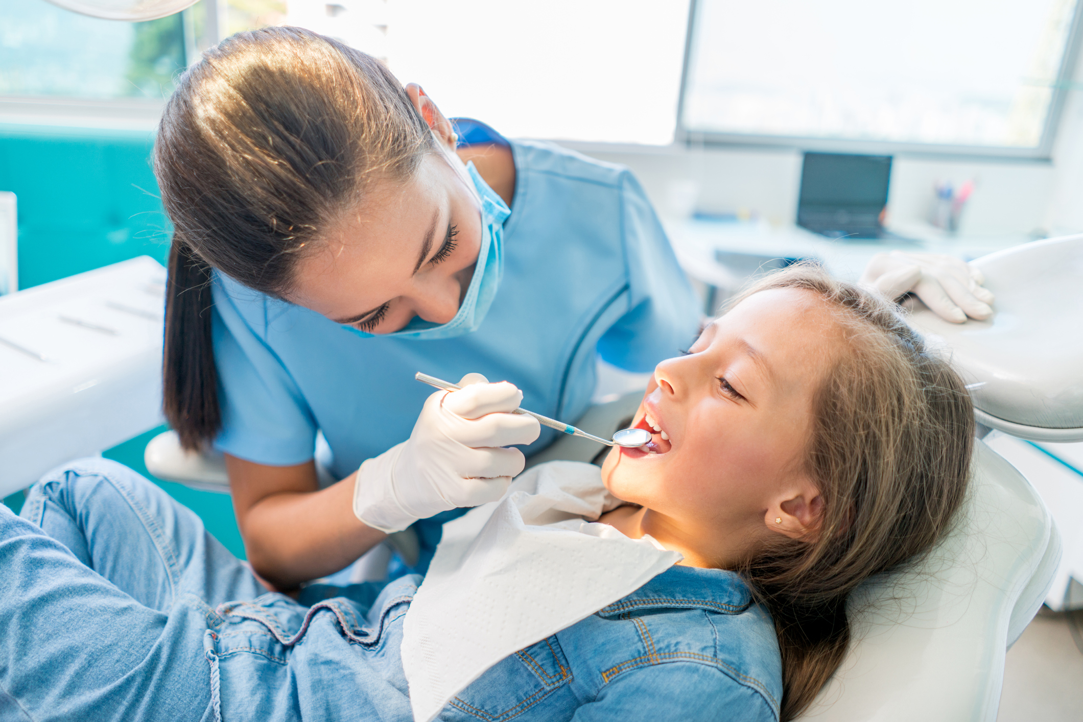 Female dentist wearing a mask and examining a pediatric female patient.