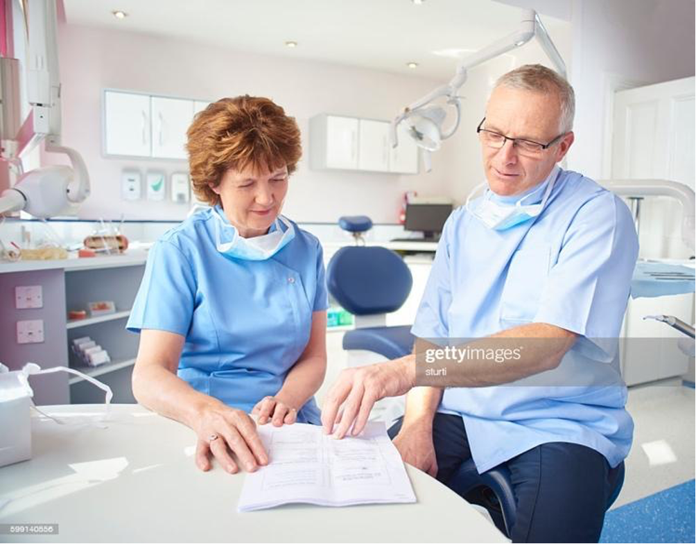 A male and female dentist sit in a dental office as they peruse paperwork and discuss dental practice membership programs.