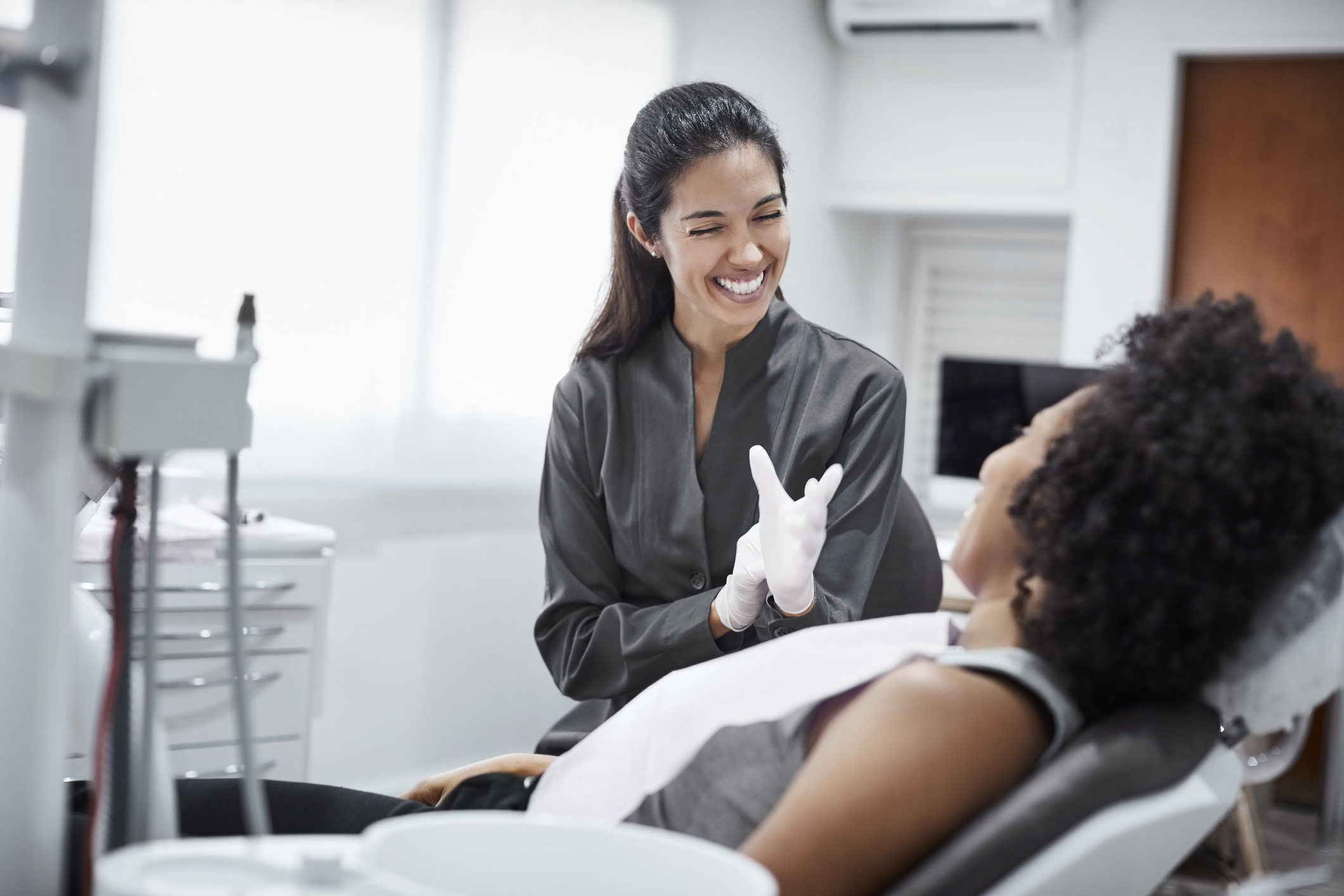 Female dentist putting on latex gloves and smiling at a patient in a dental chair
