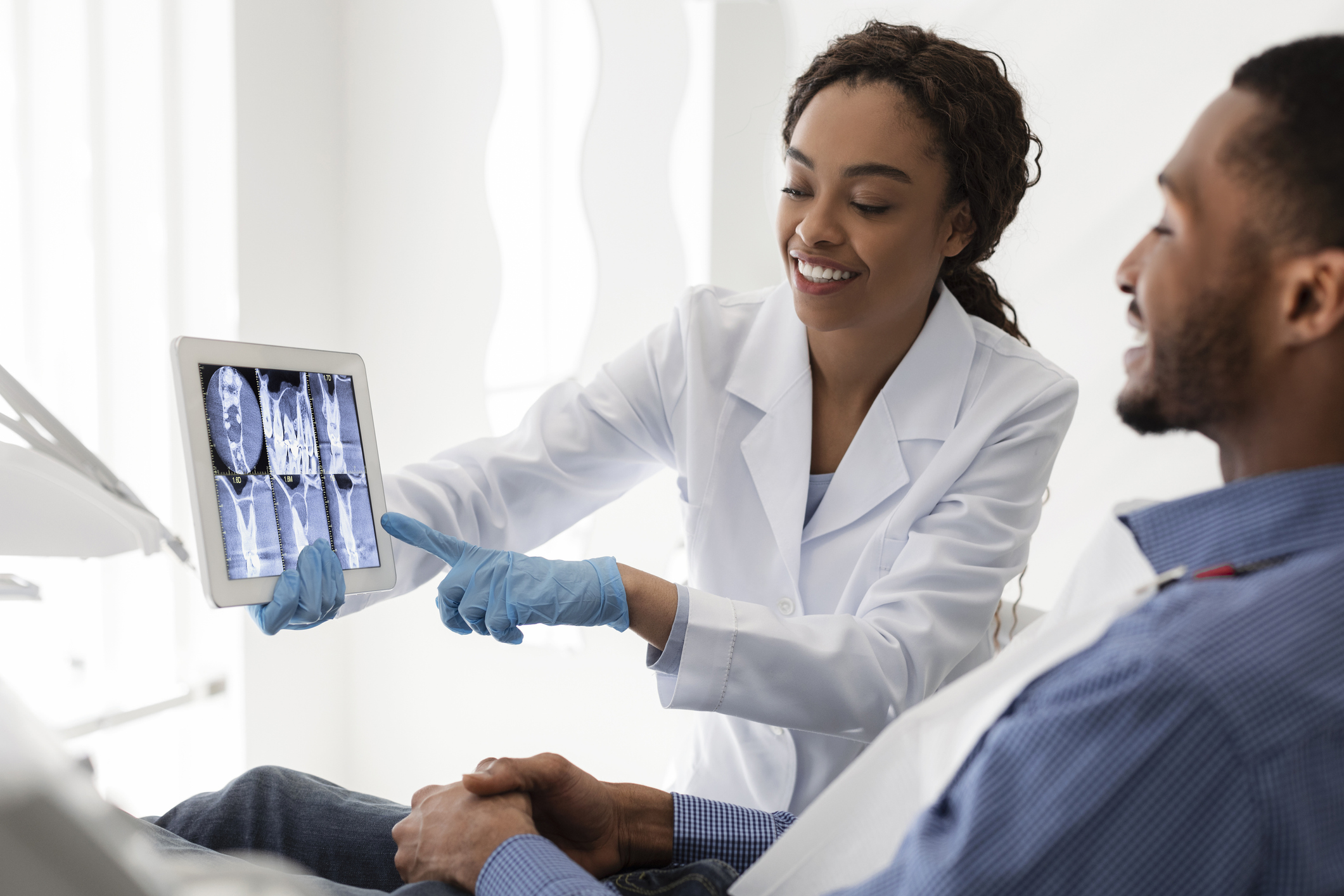 A female dentist shows dental scans on a tablet to a patient seated on a dentist's chair as part of a broader customer or patient advocacy strategy.